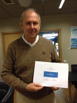 Lennart Åhs visar upp Färjestad BK:s Blå Rummet Stiftelsens logga. Den består av ett blått hjärta med en öppen dörr. Foto: Marie Angle/fbkbloggen